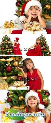 Девочка в шапке санты возле новогодней ёлки - Stock photo